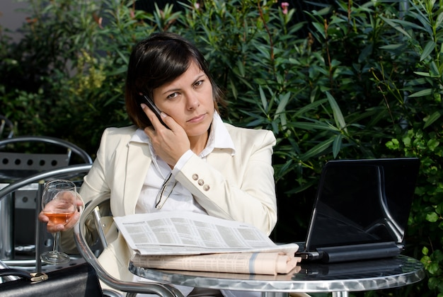 Imprenditrice parlando al telefono mentre si lavora con i documenti e in possesso di un bicchiere di vino
