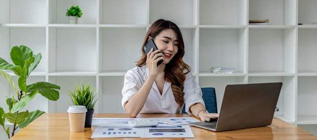 Businesswoman talking on the phone with her business partner, she sits in a private room, in a room decorated with plants and bookshelves on the desk with work papers and laptop. asian women concept.