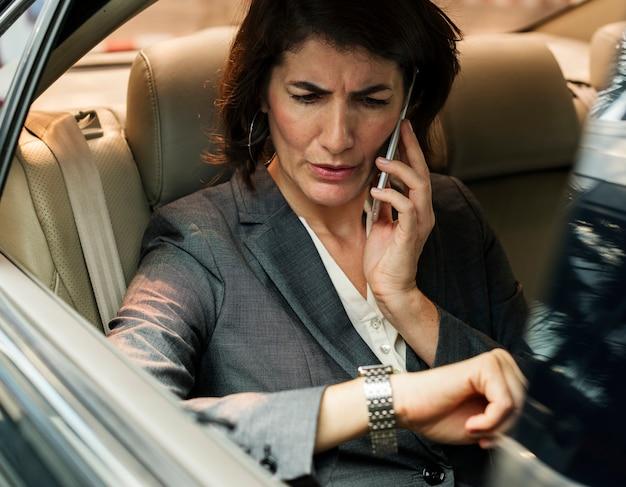 Businesswoman talking using phone car inside
