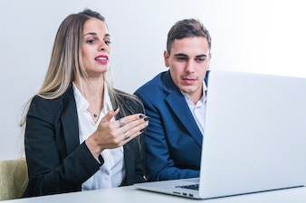 Businesswoman talking with businessman looking at laptop
