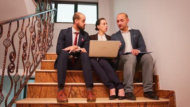 ビジネスビルの階段で会社のマネージャーやオフィスの幹部と話している実業家。チームのプロの起業家は、ラップトップとタブレットを使用して、オフィスの階段で同僚と協力します。