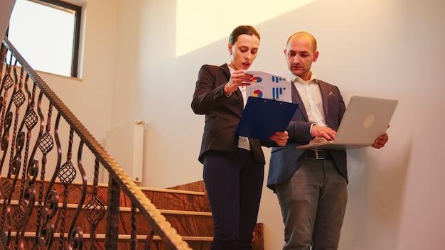 ノートパソコンを探しているビジネスビルの階段で企業のエグゼクティブマネージャーと話している実業家。現代のオフィスの階段で残業しているチームでプロの成功した起業家。