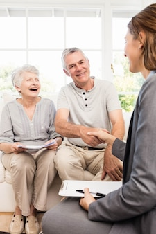 Businesswoman talking with senior couple at home