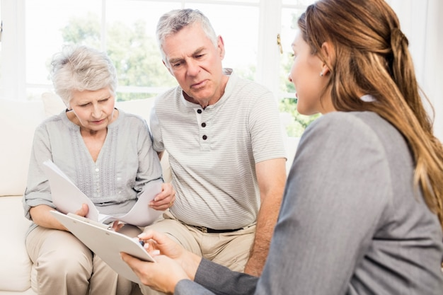 Businesswoman talking with senior couple and showing clipboard at home