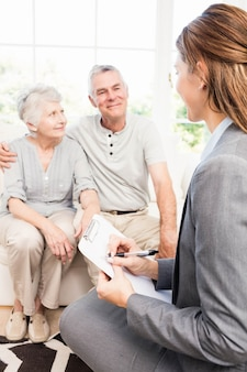 Businesswoman talking with senior couple and writing on clipboard at home