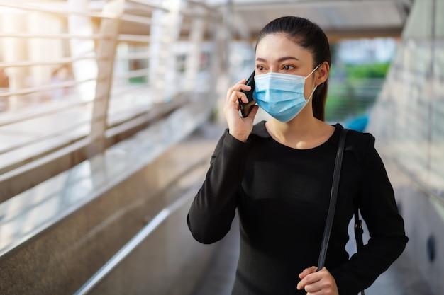 Деловая женщина разговаривает со смартфоном и носит медицинские