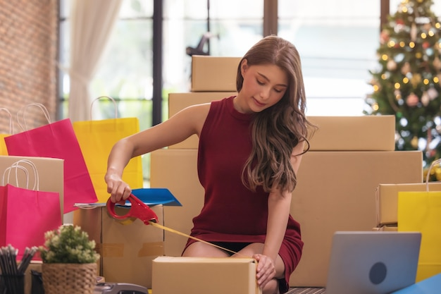 Businesswoman taping up a cardboard box, asian woman packing boxes among stack of parcels in her shopping online business at home