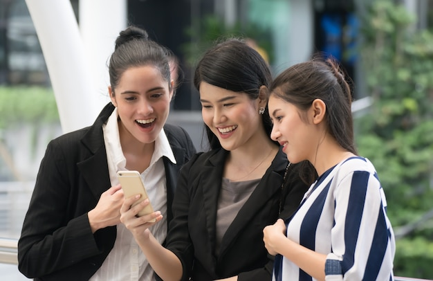 Businesswoman team in smart casual using mobile phone outdoors.