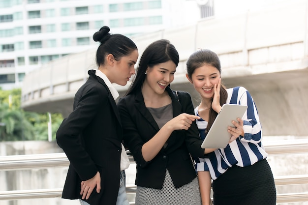 Businesswoman team in smart casual using notebook outdoors.