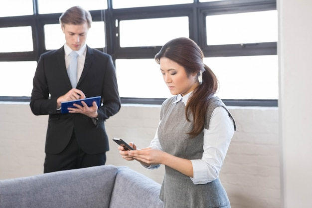 Businesswoman text messaging on smartphone and businessman using digital tablet in office
