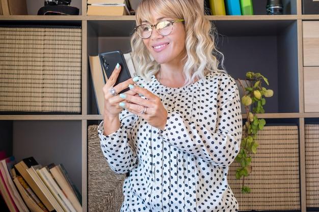 オフィスで携帯電話を使用した実業家のテキストメッセージ。スマートフォンを使用してソーシャルメディアコンテンツを見ている美しい白人女性。眼鏡のテキストメッセージや電話を使用してメッセージを読んで幸せな女性