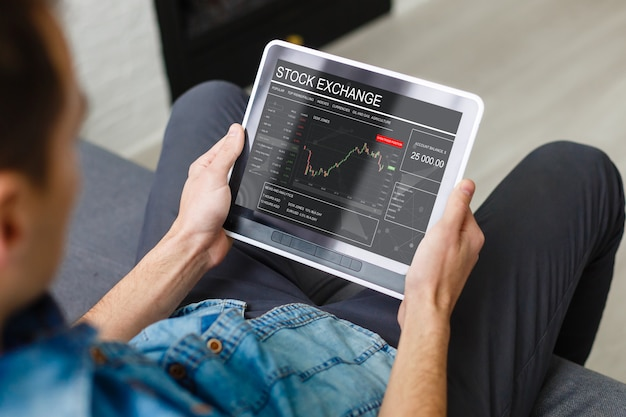 Businesswoman trading stocks with tablet and graph