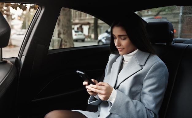 뒷좌석에 자동차로 여행하는 사업가, 회의에서 운전하는 동안 스마트 폰에서 문자 메시지를 읽고