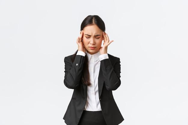 Деловая женщина пытается сосредоточиться, страдает мигренью перед важной деловой встречей. азиатская женщина-предприниматель трогает виски и морщится от боли, имея головную боль, белый фон
