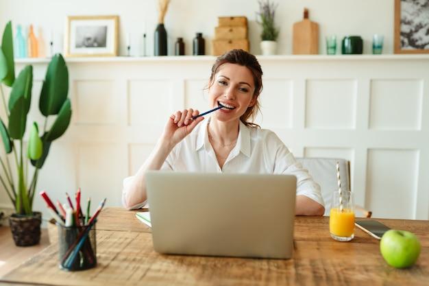 Деловая женщина, набирающая электронное письмо на ноутбуке в домашнем офисе