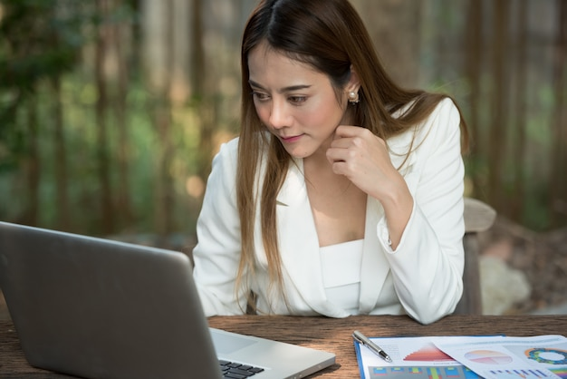 Businesswoman typing document on laptop computer.