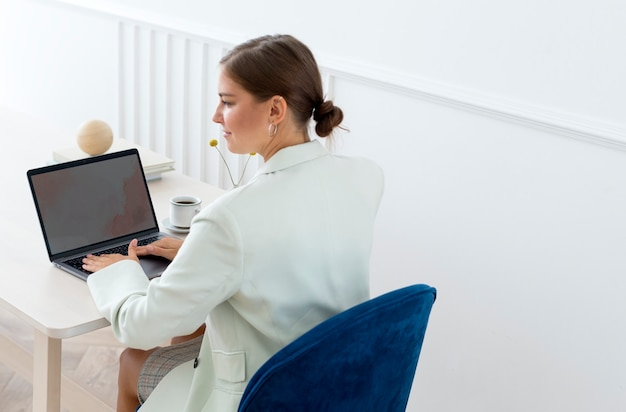 Businesswoman typing on her laptop on a wooden table