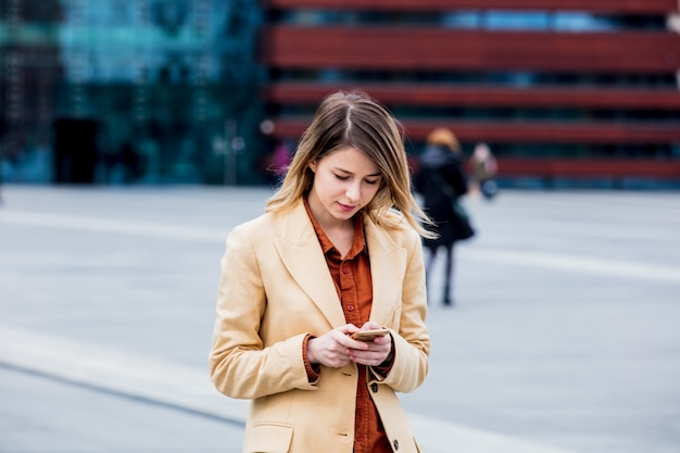 Businesswoman typing message by phone on the city square