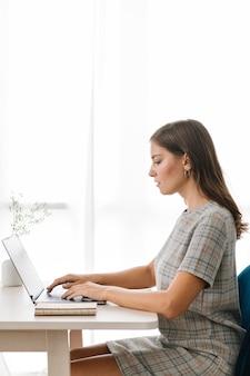 Деловая женщина, печатающая на своем ноутбуке на деревянном столе