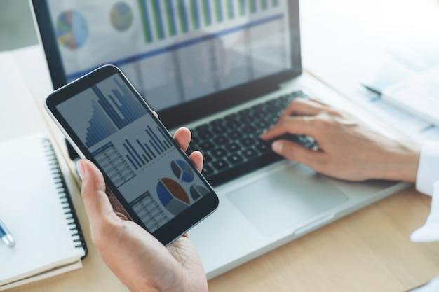 Бизнесмен использует компьютер и мобильный телефон для анализа онлайн-информации.