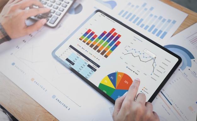 태블릿을 사용하여 회사 재무 전략 통계의 성공 개념을 분석하고 사무실에서 미래를 계획하는 사업가입니다.