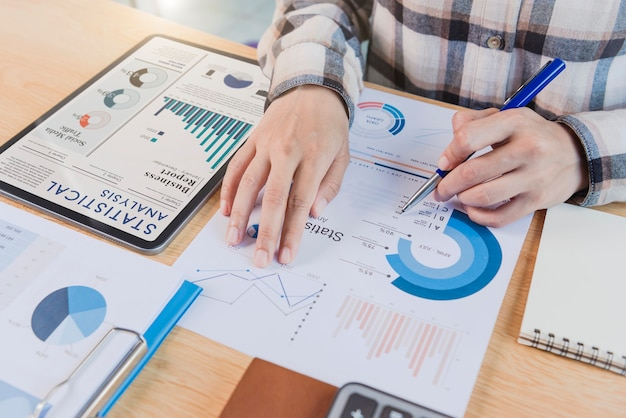 タブレットを使用してグラフ会社の財務戦略統計の成功の概念とオフィスルームでの将来の計画を分析する実業家。