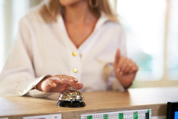 Деловая женщина, использующая звонок на стойке регистрации отеля