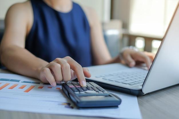 Businesswoman using calculator for analysis maketing plan
