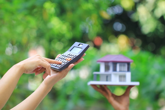 Businesswoman using a calculator and wooden house on green
