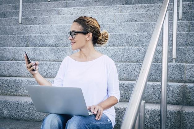 コンピューターを使用して携帯電話で話している実業家。美しい中年の女性は、ホットスポットのwifiデバイスのようなラップトップインターネット接続と携帯電話で屋外で働きます。 evで働く現代人