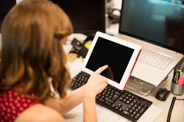オフィスの机でデジタルタブレットを使用して実業家