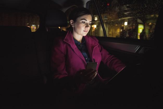 Donna di affari che per mezzo della compressa e del telefono digitali