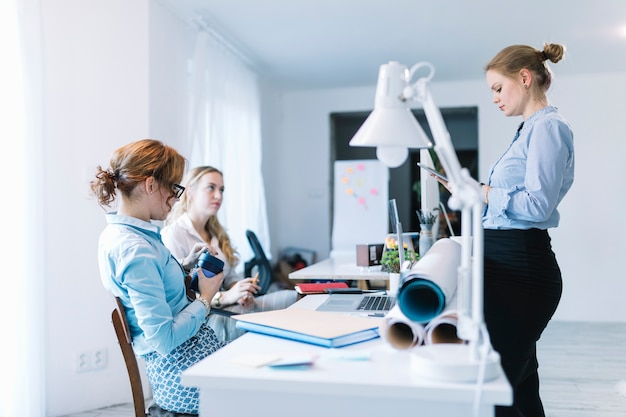 Businesswoman using digital tablet standing near her colleague sitting in office