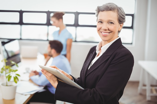 Businesswoman using digital tablet with colleagues