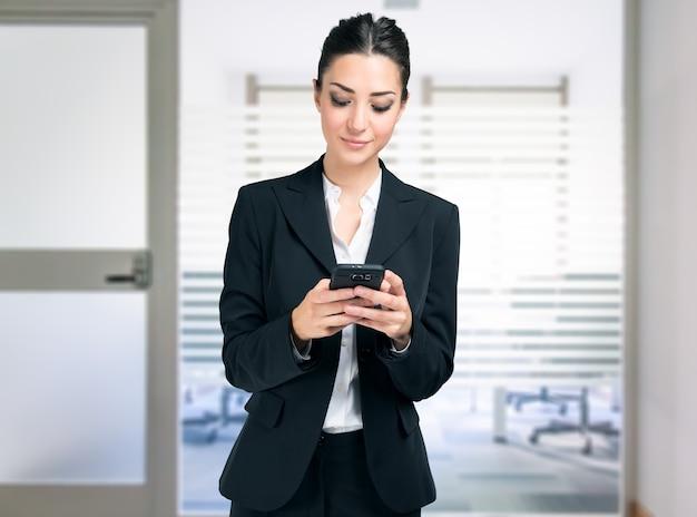 オフィスで彼女の携帯電話を使用して実業家