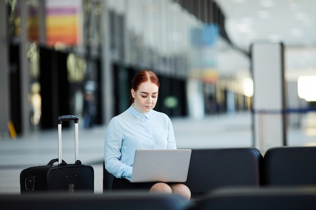 Businesswoman using laptop in airport