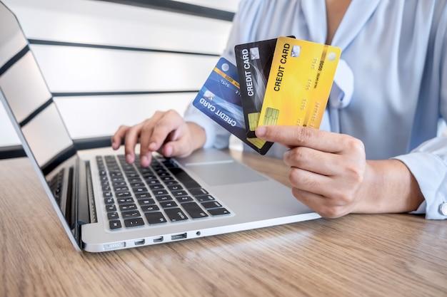 ラップトップを使用して詳細ページを支払うためのクレジットカードを保持している実業家がオンラインショッピングでの購入とカード情報を入力するためのセキュリティコードを表示