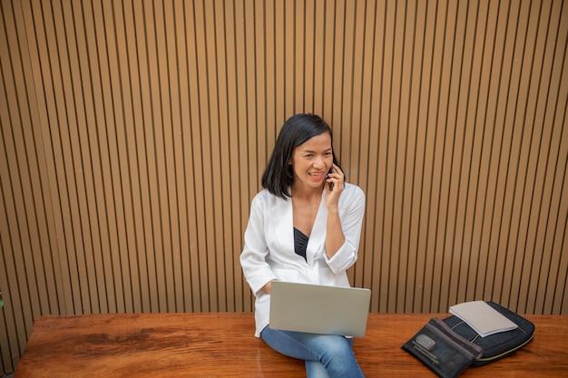 ラップトップコンピューターを使用して携帯電話で話している実業家