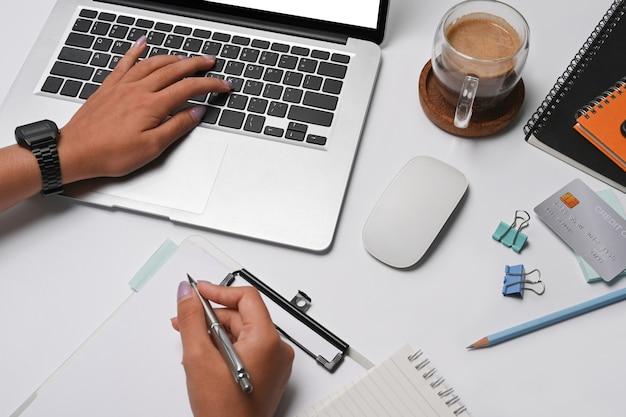 Деловая женщина, использующая портативный компьютер и написание информации о документах.