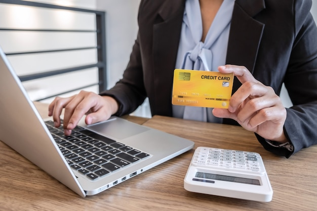 Businesswoman using laptop and holding credit card for paying detail page display online shopping purchase and entry security code to inputting card information.