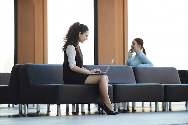 Businesswoman using laptop in lobby