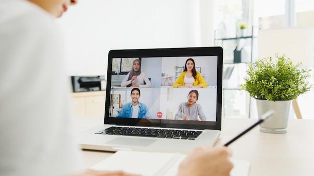 ノートパソコンを使用している実業家は、自宅の居間で仕事をしながら、ビデオ通話会議の計画について同僚と話します。