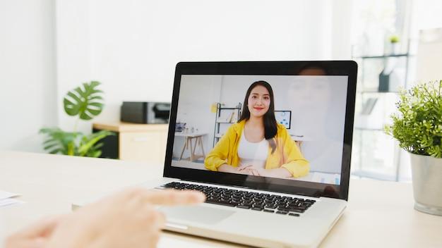 랩톱을 사용하는 사업가 거실에서 집에서 작업하는 동안 화상 통화 모임 계획에 대해 동료에게 이야기합니다.