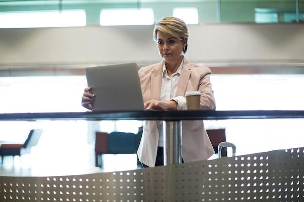 Imprenditrice utilizzando laptop in area di attesa