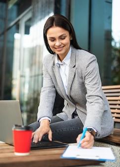 屋外でコーヒーを飲みながらノートパソコンを使用して実業家
