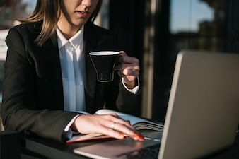 Businesswoman using laptop while having cup of coffee
