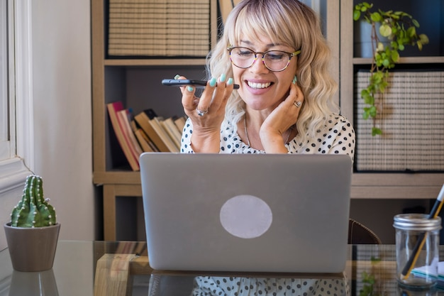 사무실에서 휴대 전화로 얘기 하는 동안 노트북을 사용 하는 사업가. 직장에서 바쁜 여자입니다. 음성 통화, 스피커 또는 음성 인식을 통해 사무실에서 휴대폰으로 말하는 여성.