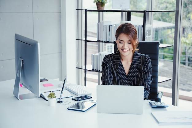 Businesswoman using laptop while working in her office.
