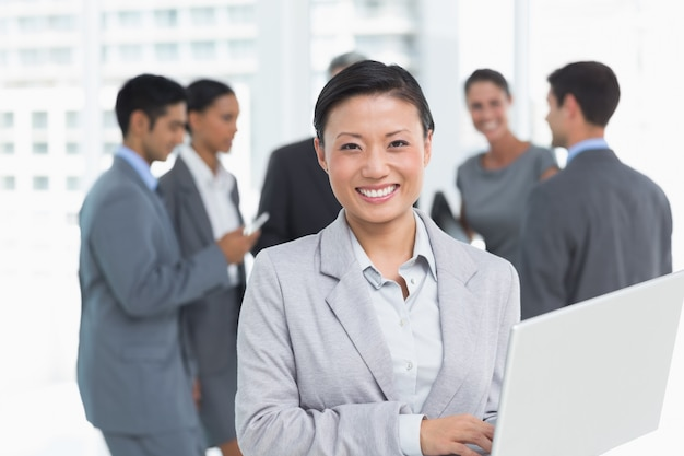 Businesswoman using laptop with colleagues behind