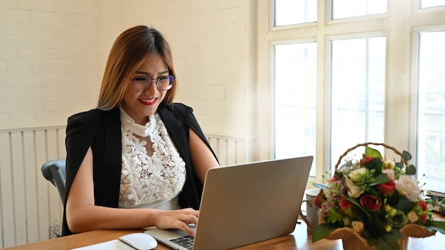 Businesswoman using laptop on wood table.